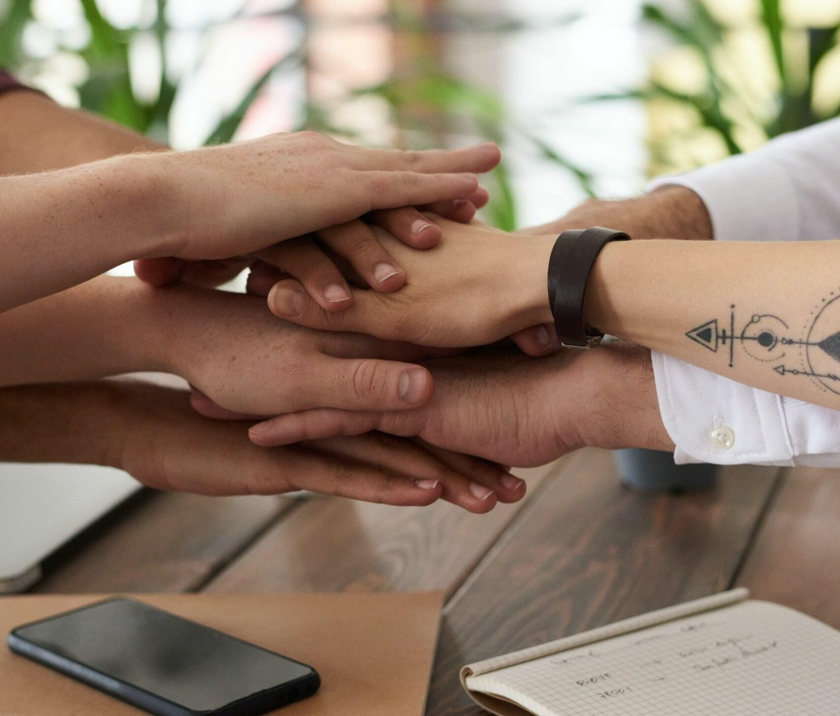 a group of people stacking their hands together