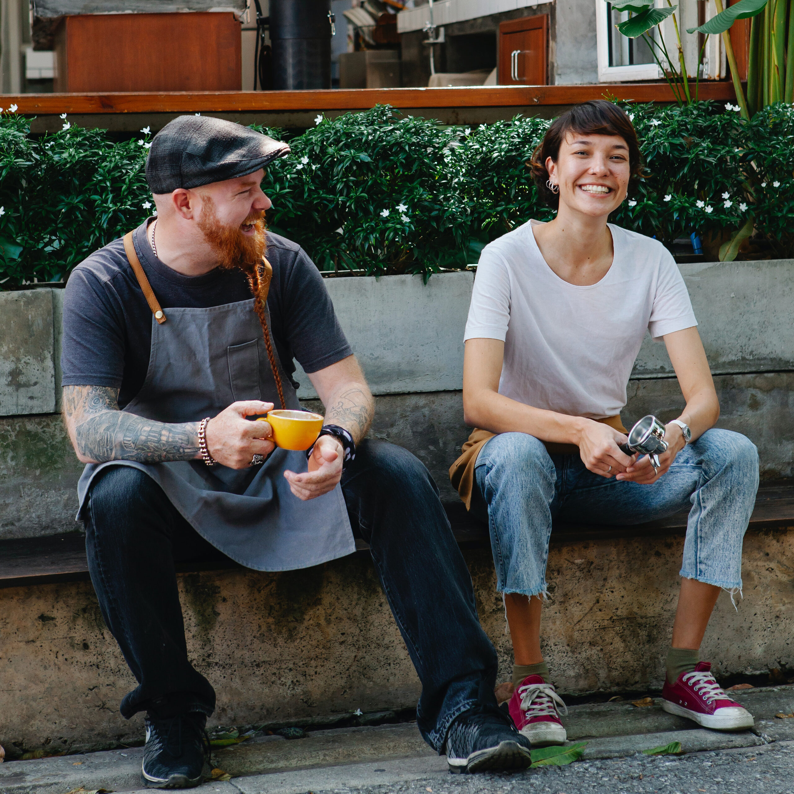 a man and woman sitting down drinking coffee and smiling for the camera